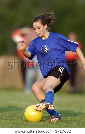 Teen girl soccer player makes a move with a yellow soccer ball