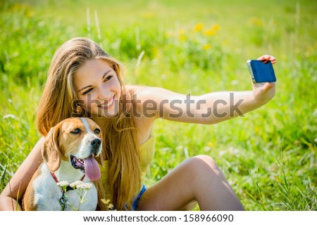 Teen girl taking photo of herself and her dog with mobile phone camera