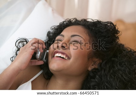 Teen girl talking on mobile phone from bed