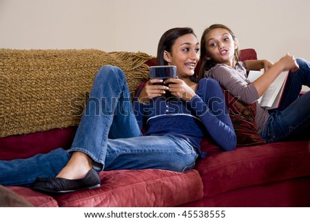 Teen girl texting on mobile phone while younger sister looks over her shoulder