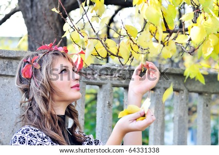 stock photo : teen girl touching leaves in the autumn park