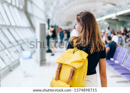 Teen girl waiting for international flight in airport departure terminal. Young passenger with backpack travelling on airplane. Teenager tourizm abroad alone concept. #1374898715