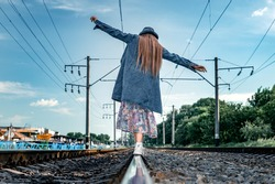 Teen girl walks by rail. Girl is walking around the rails