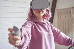 Teen girl wear vr goggles hold controller playing virtual reality video game using digital innovation headset app. Young adult woman gamer pink hair play 360 3d videogame immersive simulator at home.
