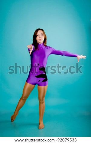 Teen girl wearing a violet gymnastic clothes dancing. Isolated on turquoise background with clipping path