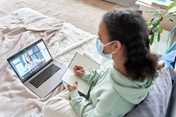 Teen girl wearing face mask remote studying online with web teacher at home. African teenager distance learning watching webinar, virtual school class with tutor using laptop elearning during covid.