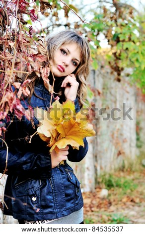 teen girl wearing leather jacket with autumn leaves