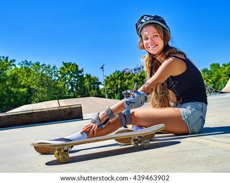 Teen girl wearing skateboard helmet fall down near her skateboard outdoor.