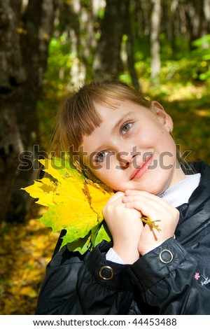 teen girl with autumn leafs in hands