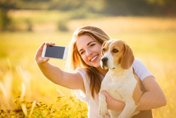 Teen girl with beagle dog taking selfie photo by her smartphone, outdoor in sunny nature