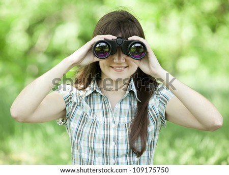 Teen girl with binocular at green grass