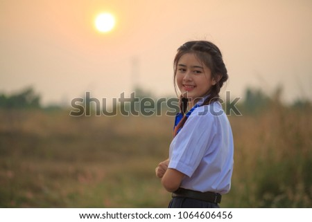teen girl with braided hairstyle and wearing student uniform ,her smiling happy standing outdoors with sunset sky, relaxed after stress in school class room,vintage tone, Space for text