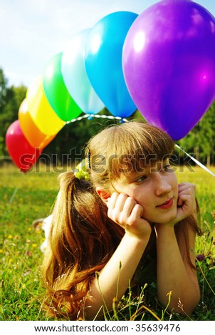 Teen girl with colorful balloons on the meadow