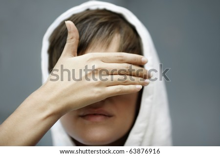 teen girl  with eyes covered by hand, selective focus on foreground