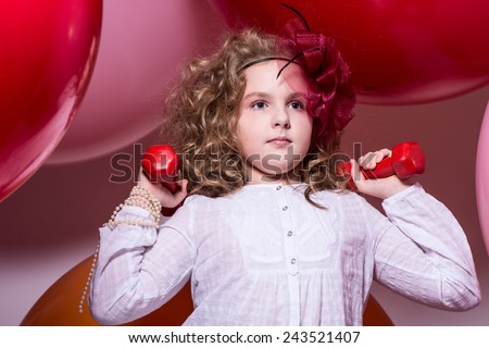Teen girl with red dumbbells. Exercise, fitness on a background of large rubber balls