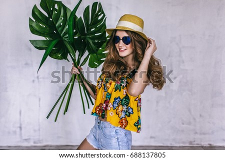 teen girl with tropical leaves in sunglasses and summer hat, summertime teen fashion