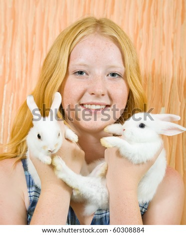 Teen  girl with two pet rabbits smiling indoor
