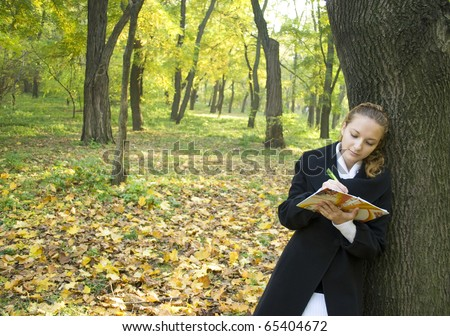 stock photo : Teen girl writes a poetry in gold autumn park
