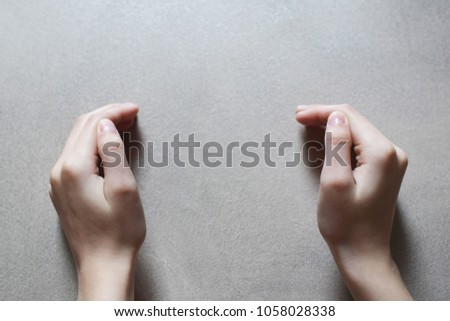 Teen girls both hands on grunge grey beige colored cocrete wall background with copy space for text between hands.