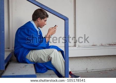 Teen Graduate in a Blue robe sending a text