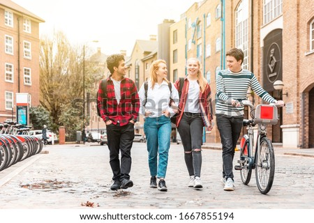 Teen group of friends walking in the city and pushing a bike - Multiracial group of teenagers best friends enjoying time together in London - Lifestyle and friendship in London