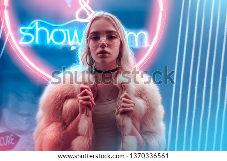 Teen hipster girl in stylish glasses and fur posing near neon sign on street, female teenager fashion model woman with beautiful face looking at camera in city night light glow, back to 80s, portrait