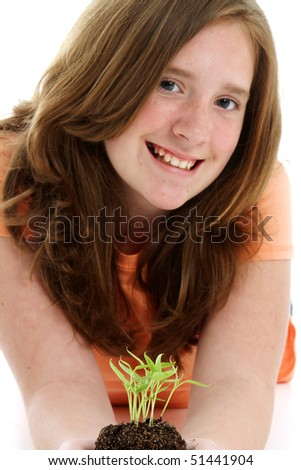 Teen holding a plant in pile of dirt