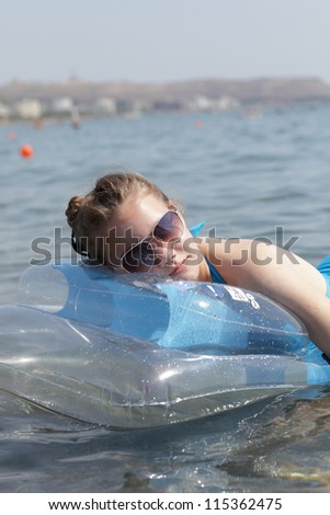 Teen is resting on inflatable mattress in the sea, Greece