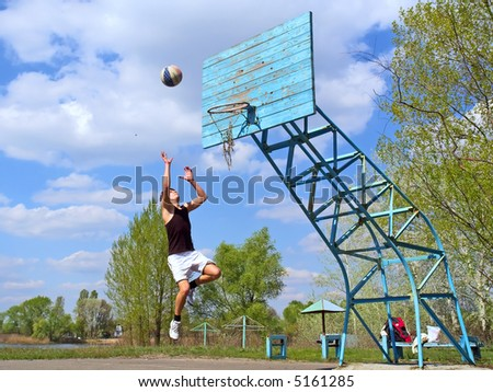 Teen jumps after basketball in early spring park. Shot in Ukraine.