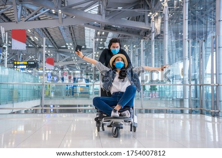 Teen lovers wear a mask to protect against Corona virus. covid19 disease, sitting on a trolley luggage, cheerful fun enjoy to travel at the airport. New normal ,Vacation and travel concept