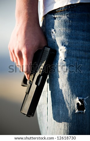 Teen male holding modern 9mm handgun, limited depth of field closeup