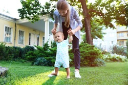 Teen nanny with cute baby on green grass outdoors