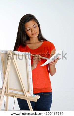 Teen painting a canvas on white background