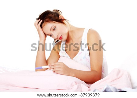 Teen pretty depressed girl checking her pregnant test in bed.