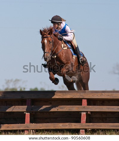 Teen rider jumps over an obstacle on a cross country course during a practice ride