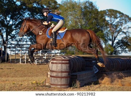 Teen rider leaps across a barrel jump on a cross country course