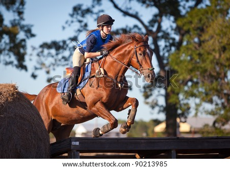 Teen rider leaps across a platform on a cross country course
