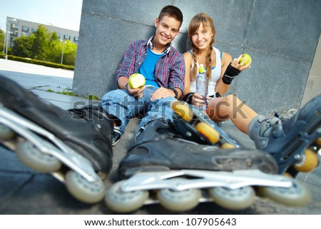 Teen roller-skaters having a snack after a good workout
