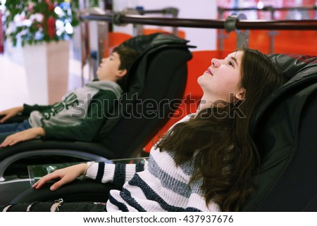 Teen Siblings Brother And Sister In Massage Chair In Shopping Mall 437937676