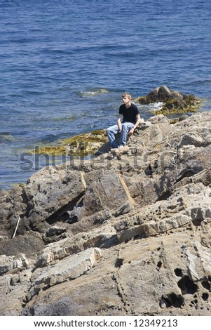 teen sitting on rocks - gulf of saint-tropez, French Riviera