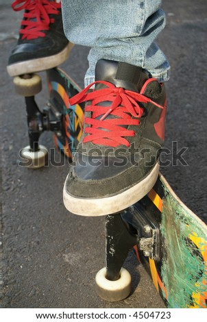 Teen skater shoes and used board on side