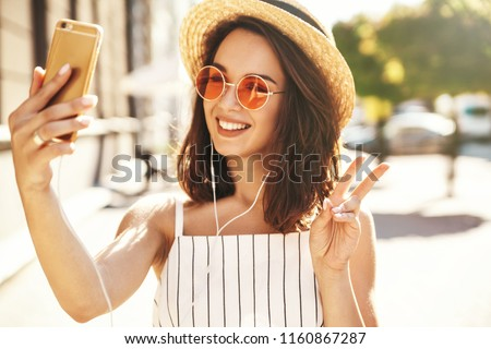Teen smiling girl in summer white hipster clothes in headphones taking selfie on smartphone on warm sunset background  #1160867287