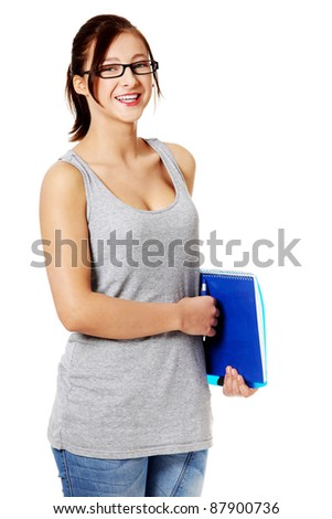 Teen student standing and holding her notebook. Isolated on white.