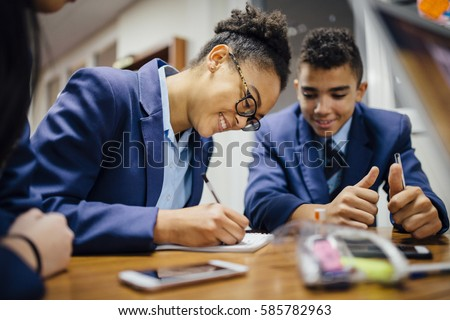 Teen students are working together and taking notes in lesson time at school.