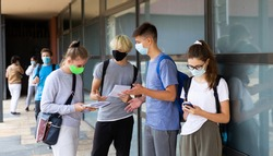 Teen students in medical face masks standing with workbooks in schoolyard during break in lessons. Concept of back to school after lockdown