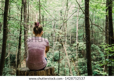 Teen Teen Girl Sitting on a Stump Looking Out into a green Forest full of trees #1428752537