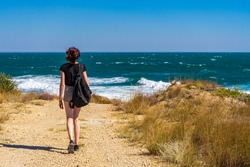 Teen tourist girl with backpack walking on country road along sea coast in sunny day. Travelling and discovering distant places of Earth. Summer vacation, trip to seaside, travel blog concept