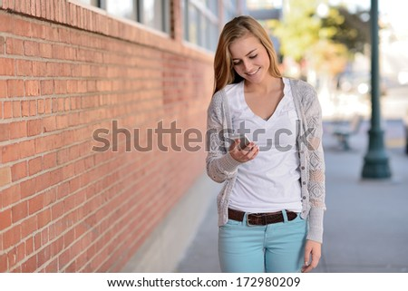 Teen using cell phone. Young woman looking at a smartphone while walking on a city street.