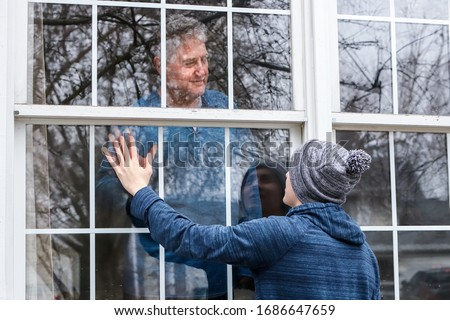 Teen visiting senior citizen quarantined in home, touching hands through the window, main focus on boy's hat and man in window