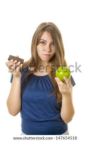 Teen with brownie and apple against a white background. - stock photo